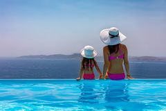 Het concept van de familievakantie: de moeder zit met haar dochter bij de pool royalty-vrije stock foto