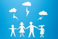 Het concept van de familieverzekering Document de de de de origamivader, moeder, zoon en dochter houden handen onder bliksemstaki stock foto
