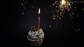 Het concept van de het feestviering van de verjaardagspartij Een cupcake met een kaars op zwarte Vuurwerk Sterretjes het branden  stock footage