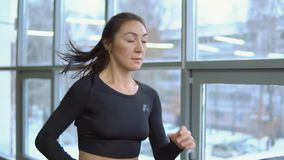 Het concept van de geschiktheid Close-up van een mooie vrouw op een tredmolen in de gymnastiek stock video