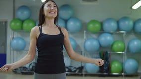 Het concept van de geschiktheid Jong vrouwentouwtjespringen in de gymnastiek stock videobeelden