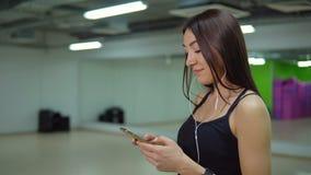 Het concept van de geschiktheid Jonge vrouw in sporten eenvormig met telefoon en in hoofdtelefoons bij de gymnastiek stock footage