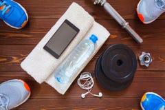 Het concept van de geschiktheid Sportmateriaal De schoenen, de handdoek, de fles water, de oortelefoons, de domoren en de telefoo Royalty-vrije Stock Foto