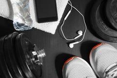 Het concept van de geschiktheid Sportmateriaal De schoenen, de handdoek, de fles water, de oortelefoons, de domoren en de telefoo Royalty-vrije Stock Afbeeldingen