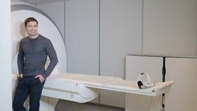 Het concept van de gezondheid het ziekenhuispatiënt dichtbij MRI, tomograph, scanner, CT machine Mannelijke glimlachende patiënt  stock video