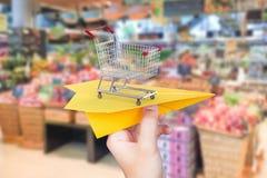 Het concept van de goederenlevering met document vliegtuigboodschappenwagentje in superma Stock Foto's