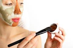 Het concept van de de huidzorg van schoonheidsprocedures Jonge vrouw die het gezichts grijze en rode masker van de modderklei toe royalty-vrije stock foto's