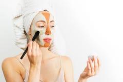 Het concept van de de huidzorg van schoonheidsprocedures Jonge vrouw die het gezichts grijze en rode masker van de modderklei toe royalty-vrije stock afbeelding