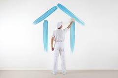 Het concept van de huisdienst schildersmens die met borstel een blauw huis trekken royalty-vrije stock fotografie