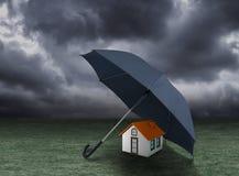 Het concept van de huisverzekering, huis onder paraplu wordt beschermd die royalty-vrije stock fotografie