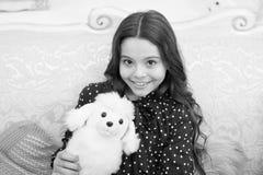 Het concept van de Kerstmisgift Van de de greep wit hond van het kind leuk klein meisje speels de pluchestuk speelgoed Het spelst stock fotografie