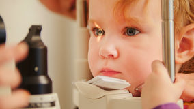 Het concept van de kind` s optometrie - het meisje controleert zicht in oog oftalmologische kliniek stock afbeelding