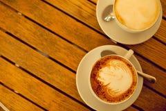 Het concept van de Lattekunst Twee koppen met cappuccino Stock Afbeeldingen