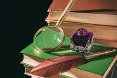 Het concept van de literatuur Inkstand met veer dichtbij vergrootglas op oude boeken tegen zwarte achtergrond stock foto