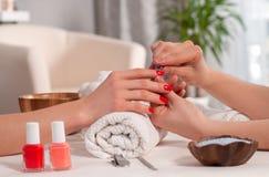 Het concept van de manicure De mooie rode spijkers van de vrouwen` s hand wiith in het kuuroord Stock Fotografie