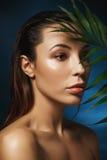 Het concept van de manier Close-up van het verbazen van vrouw op donkerblauwe achtergrond met bladeren Royalty-vrije Stock Afbeeldingen