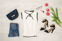 Het concept van de manier Witte blouse, blauwe handtas, glazen, lippenstift, zwarte schoenen en roze tulpen Hoogste mening, licht Stock Fotografie