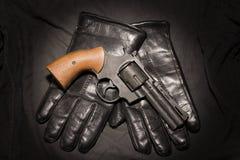 Het concept van de misdaad Zwart kanon met leerhandschoenen op donkere doek stock afbeelding