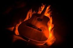 Het concept van de muziek Akoestische die gitaar op een donkere achtergrond onder lichtstraal met rook met exemplaarruimte wordt  stock foto's