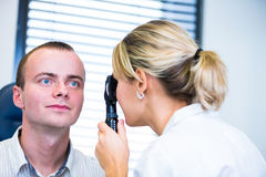 Het concept van de optometrie - knappe jonge mens die zijn onderzochte ogen hebben stock afbeelding