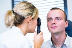 Het concept van de optometrie - knappe jonge mens die zijn onderzochte ogen hebben royalty-vrije stock afbeeldingen