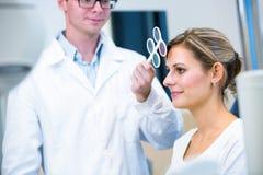 Het concept van de optometrie - vrij jonge vrouw die haar onderzochte ogen hebben stock afbeelding