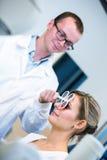 Het concept van de optometrie - vrij jonge vrouw die haar onderzochte ogen hebben stock fotografie