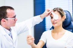 Het concept van de optometrie - vrij jonge vrouw die haar onderzochte ogen hebben royalty-vrije stock afbeelding