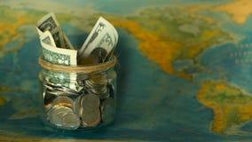 Het concept van de reisbegroting Geld voor vakantie in glaskruik wordt bespaard op de achtergrond die van de wereldkaart stock footage