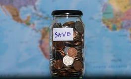 Het concept van de reisbegroting Geld voor vakantie in glaskruik wordt bespaard op de achtergrond van de wereldkaart, exemplaarru royalty-vrije stock afbeelding
