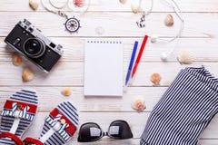 Het concept van de reisvakantie met sandals, hoofdtelefoons, zonnebril, camera, zeeschelpen, notitieboekje en gestreepte t-shirt stock foto's