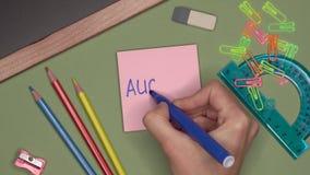 Het concept van de school De hand die van de vrouw AUGUSTUS op blocnote schrijven stock video