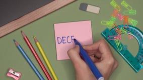 Het concept van de school De hand die van de vrouw DECEMBER op blocnote schrijven stock footage