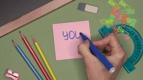 Het concept van de school De hand die van de vrouw U KAN op blocnote schrijven stock video