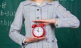 Het concept van de schooldiscipline Programma en regime De wekker in vrouwelijke handen sluit omhoog Lerarenattributen De grote k royalty-vrije stock foto's