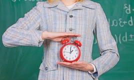 Het concept van de schooldiscipline Programma en regime De wekker in vrouwelijke handen sluit omhoog Lerarenattributen De grote k stock fotografie
