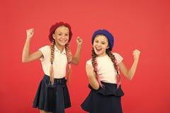 Het concept van de schoolmanier Leerling die eenvormige van de meisjesslijtage formele en barethoeden glimlachen Het internationa royalty-vrije stock afbeelding