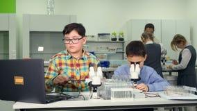 Het concept van de schoolwetenschap Basisschoolstudenten die een wetenschapsexperiment met slakken doen stock video