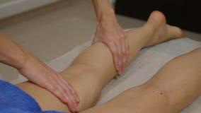 Het concept van de schoonheid Jonge vrouw die been en fet massage hebben De masseur kneedt de voet en het been van een jong mooi  stock videobeelden