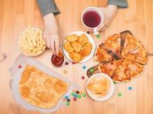 Het concept van de snel voedselongezonde kost Tienerjongen die goudklompjes, pizza, chi eten royalty-vrije stock foto