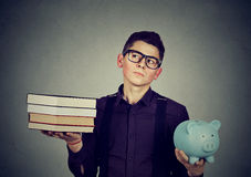 Het concept van de studentenlening Mens met stapel van het hoogtepunt van het boekenspaarvarken van schuld stock fotografie