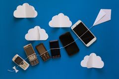 Het concept van de technologieevolutie Uitstekende en nieuwe telefoons die op document vlieger op blauwe hemel vliegen royalty-vrije stock foto's