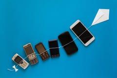 Het concept van de technologieevolutie Uitstekende en nieuwe telefoons die op document vlieger op blauwe hemel vliegen royalty-vrije stock foto