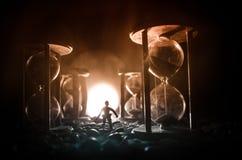 Het concept van de tijd Silhouet van een mens die zich tussen zandlopers met rook en lichten op een donkere achtergrond bevinden stock foto