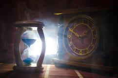 Het concept van de tijd Silhouet van Zandloperklok en oude uitstekende houten klok met pijl en rook op donkere achtergrond met he Royalty-vrije Stock Fotografie