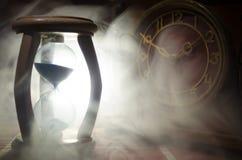 Het concept van de tijd Silhouet van Zandloperklok en oude uitstekende houten klok met pijl en rook op donkere achtergrond met he Royalty-vrije Stock Afbeeldingen