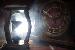 Het concept van de tijd Silhouet van Zandloperklok en oude uitstekende houten klok met pijl en rook op donkere achtergrond met he Royalty-vrije Stock Foto