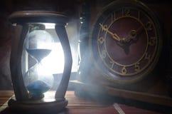 Het concept van de tijd Silhouet van Zandloperklok en oude uitstekende houten klok met pijl en rook op donkere achtergrond met he Royalty-vrije Stock Afbeelding