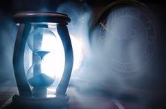 Het concept van de tijd Silhouet van Zandloperklok en oude uitstekende houten klok met pijl en rook op donkere achtergrond met he Stock Foto's