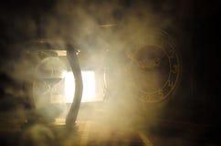 Het concept van de tijd Silhouet van Zandloperklok en oude uitstekende houten klok met pijl en rook op donkere achtergrond met he Stock Foto